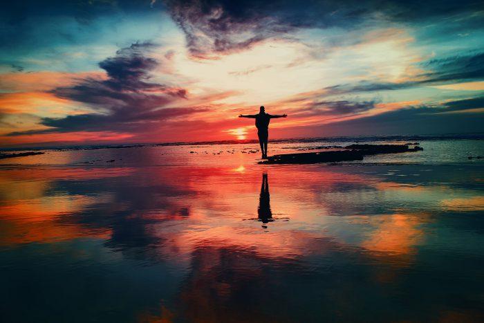 homme levant les bras au soleil dans un signe d'épanuissement